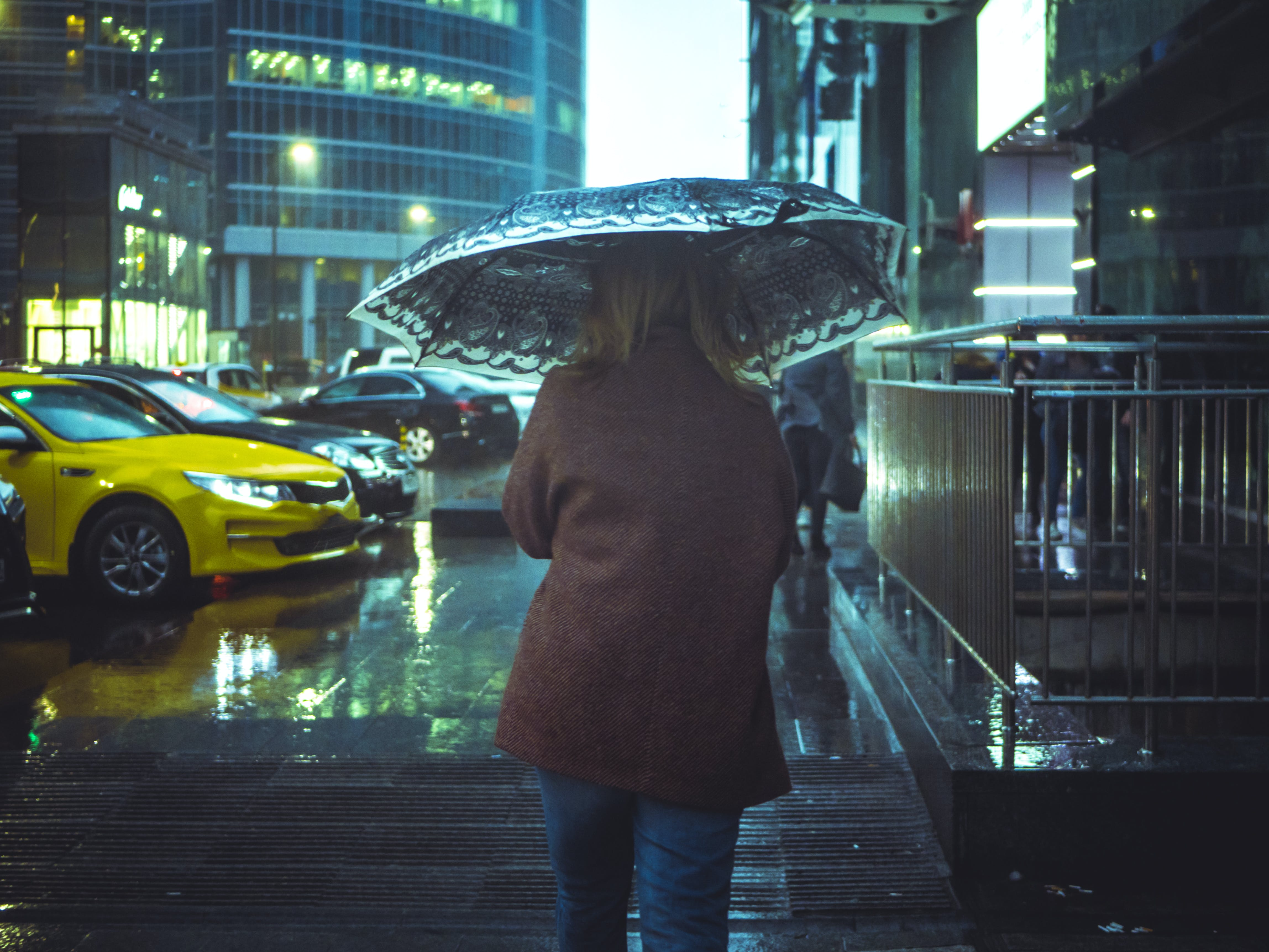 Woman Walking in Street With Umbrella during Nighttime