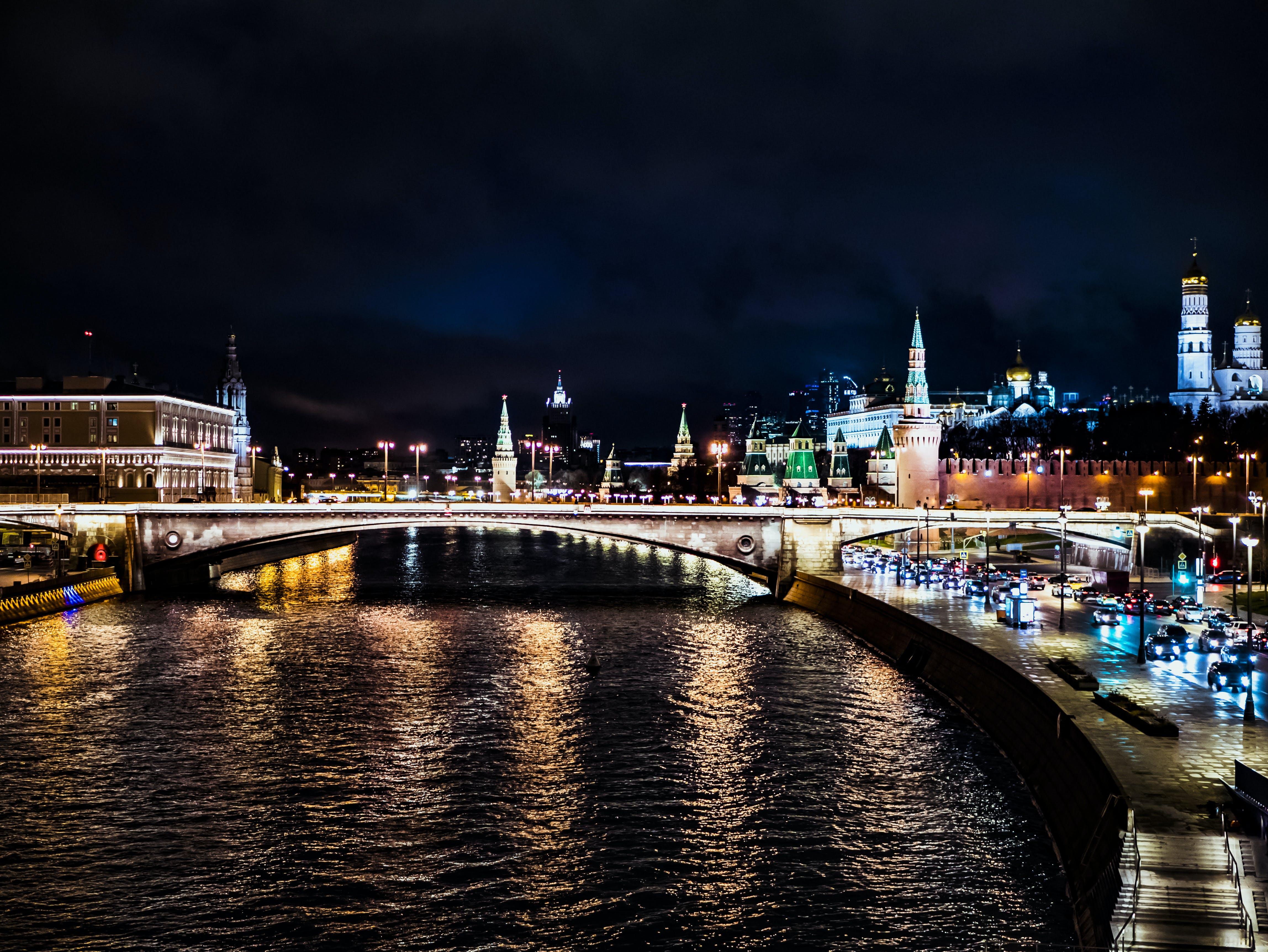 Lighted Bridge Across Body of Water Under Night Sky