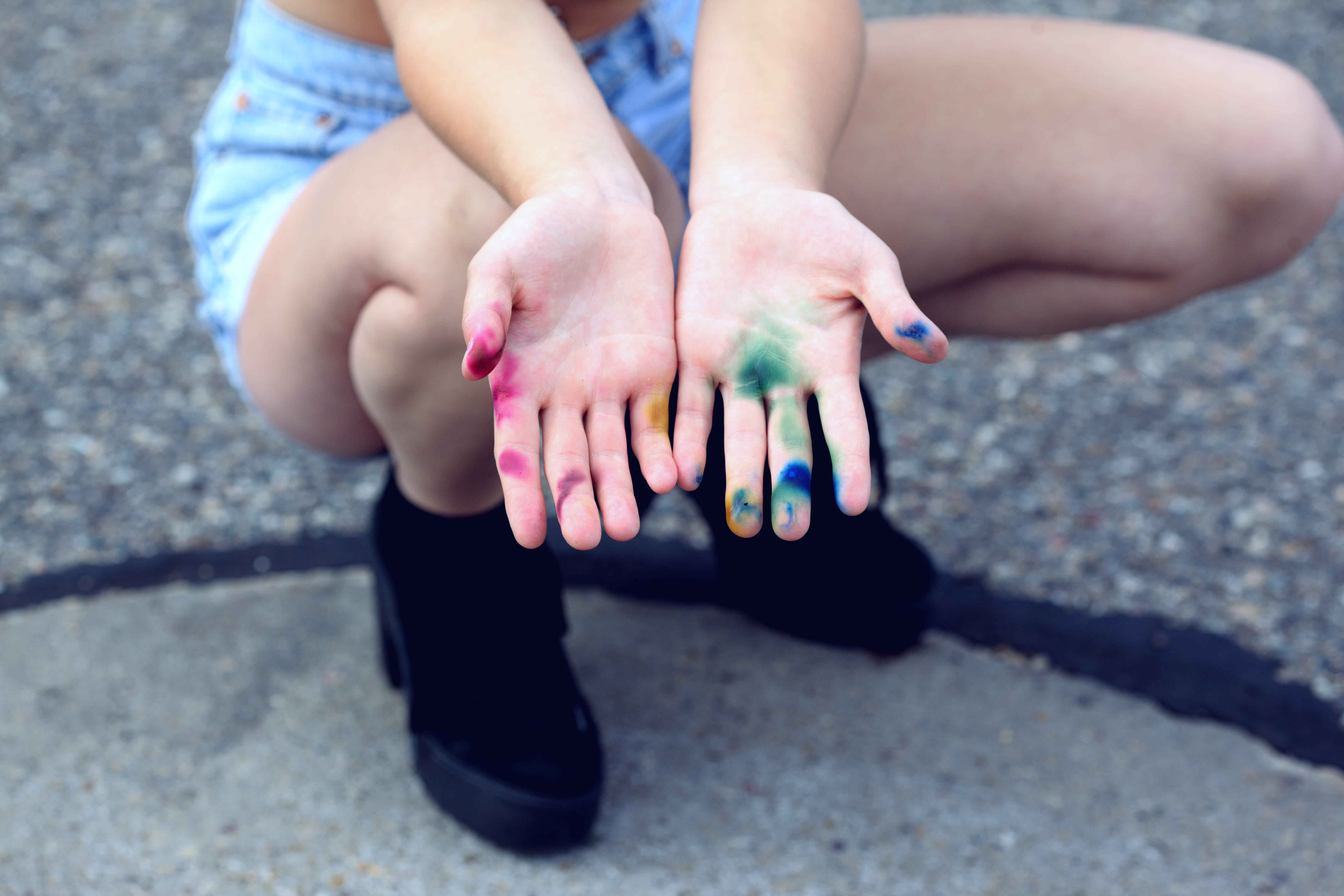 Woman Squatting Holding Out Her Hands With Assorted Paints