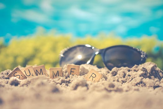 Macro Photography of Black Sunglasses on Sand