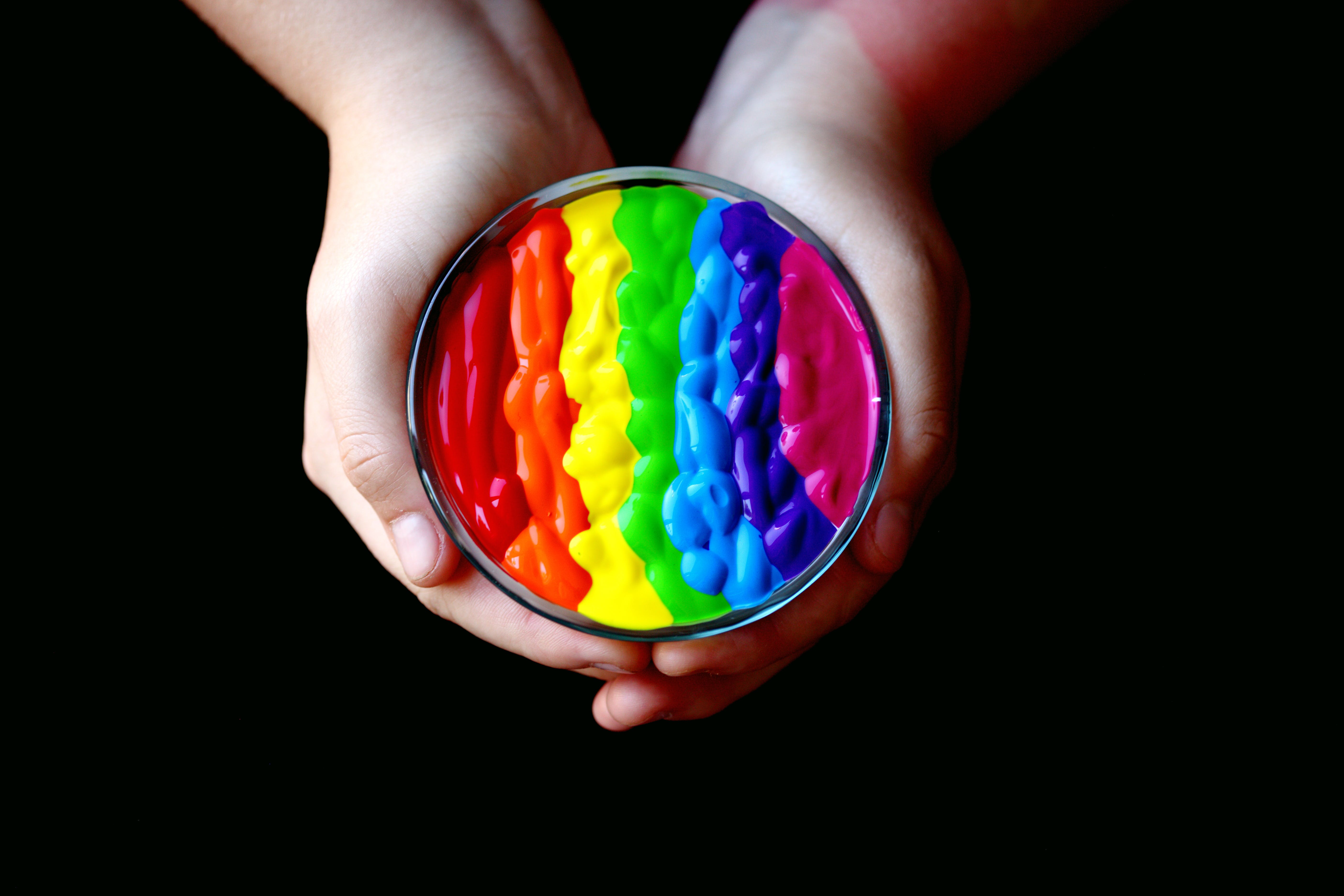 Person Holding Multicolored Container