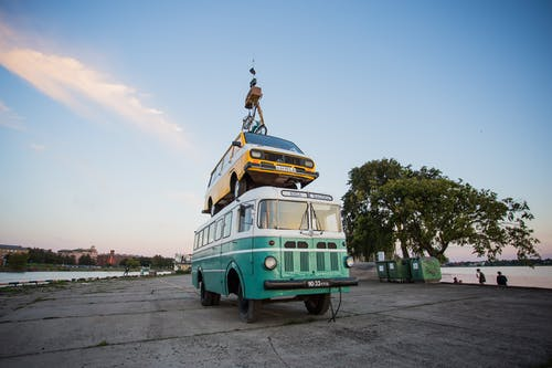 Teal Bus With Yellow Car on Roof