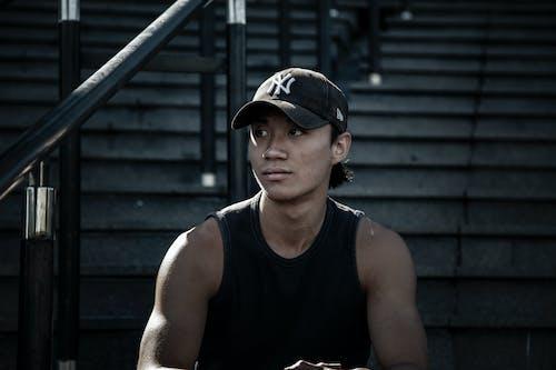 Kostenloses Stock Foto zu asiatischer mann, baseball kappe, dunkel, erwachsener
