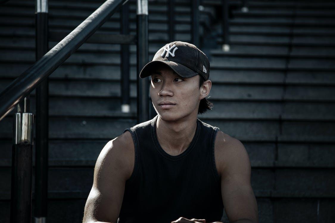 asiatischer mann, baseball kappe, dunkel
