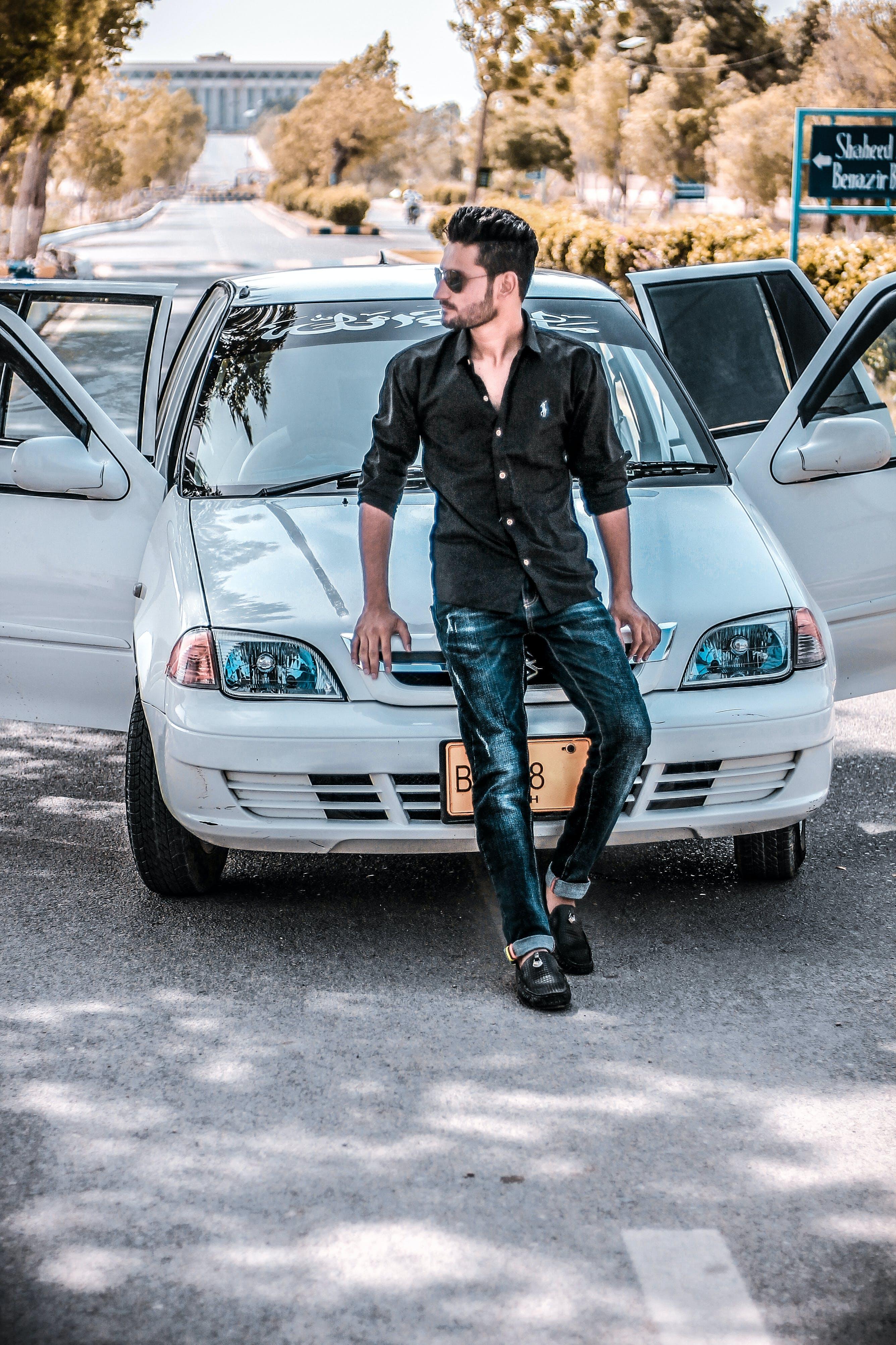 Man Sitting on White Car Hood