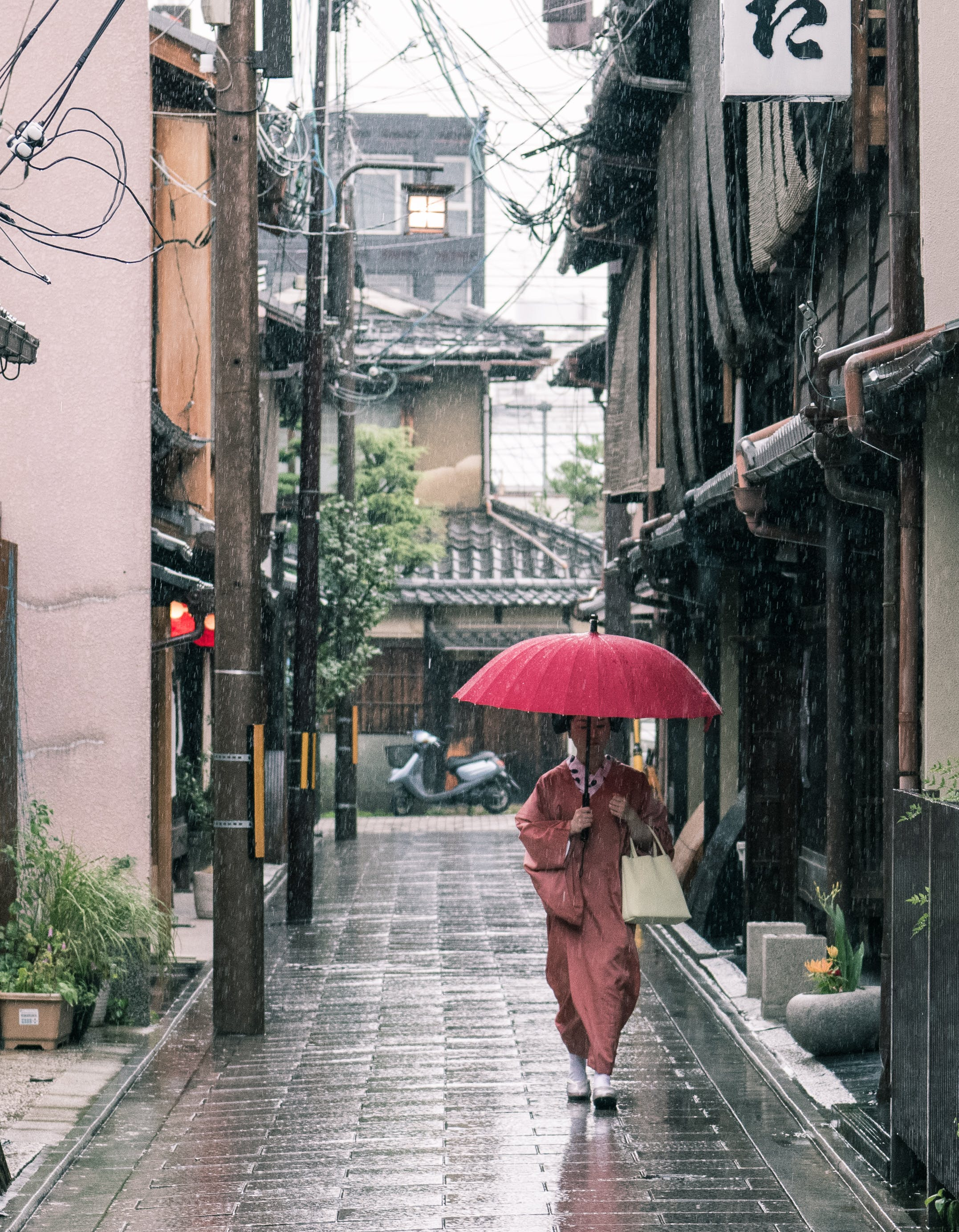 Woman in Brown Robe Holding Umbrella Walking on Concrete Pathway