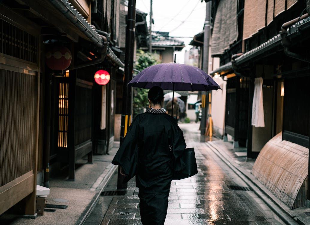 通りを歩いている紫色の傘を使用して女性
