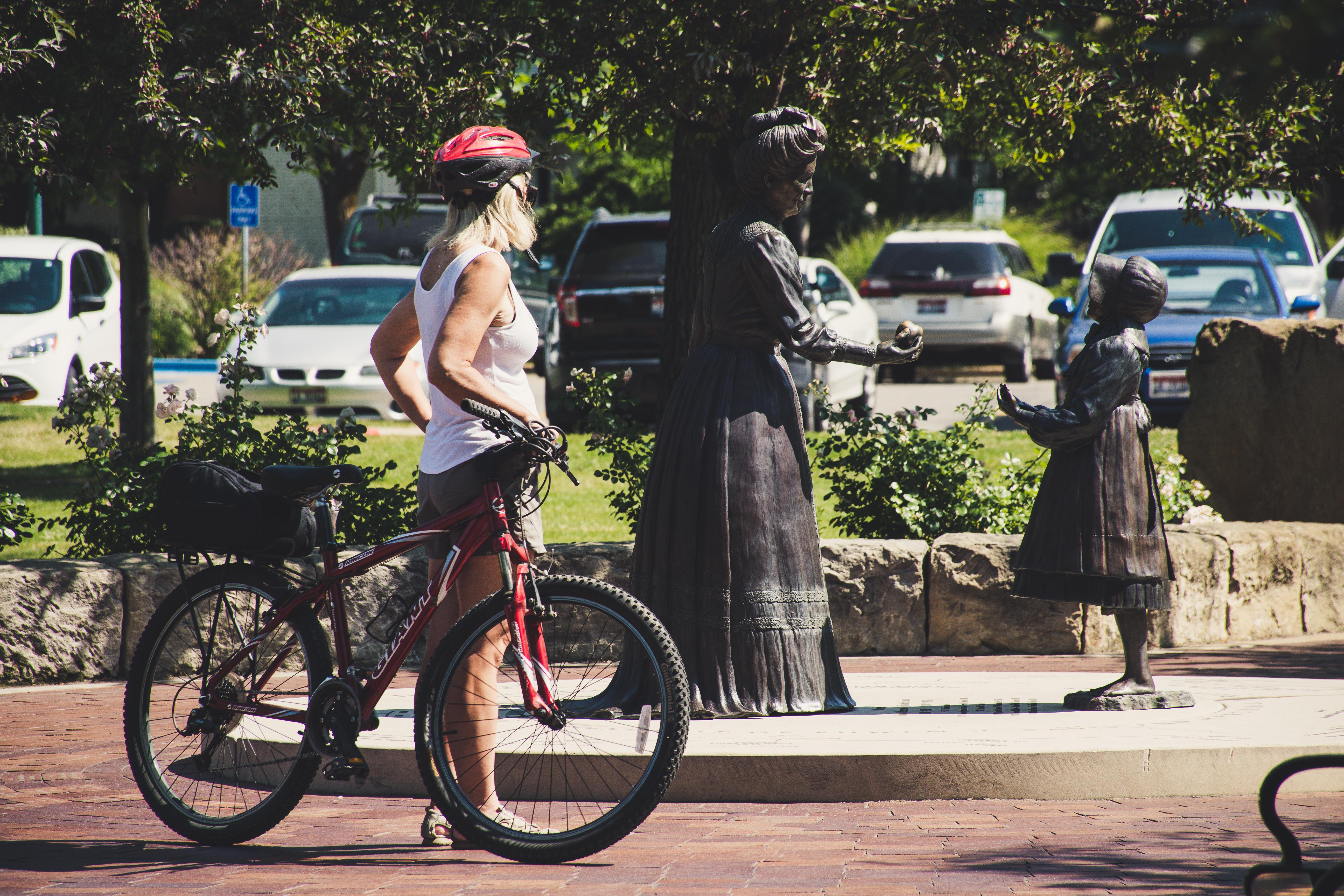 Woman Wearing White Tank Top Holding Red Hardtail Mountain Bike