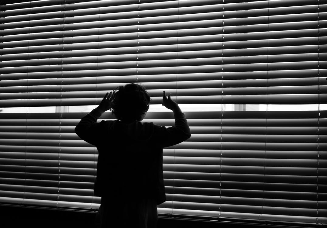 Silhouette Of Child Looking On Window Blinds