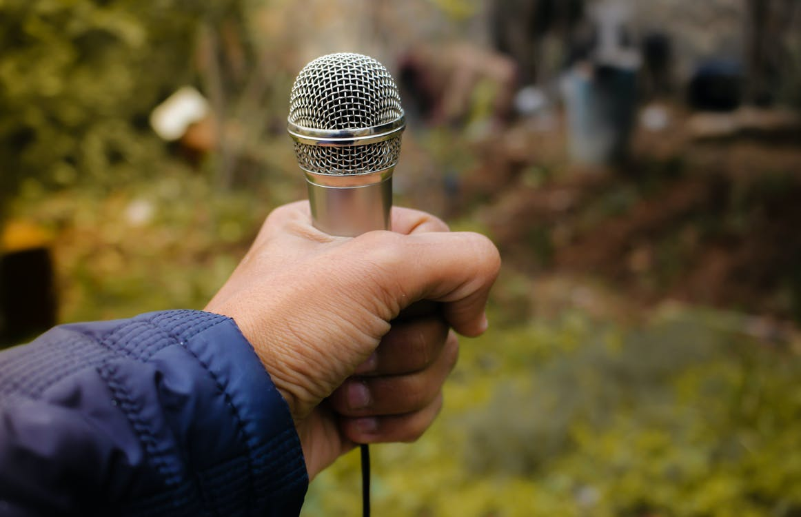 Close-Up Photography of Person holding Microphone