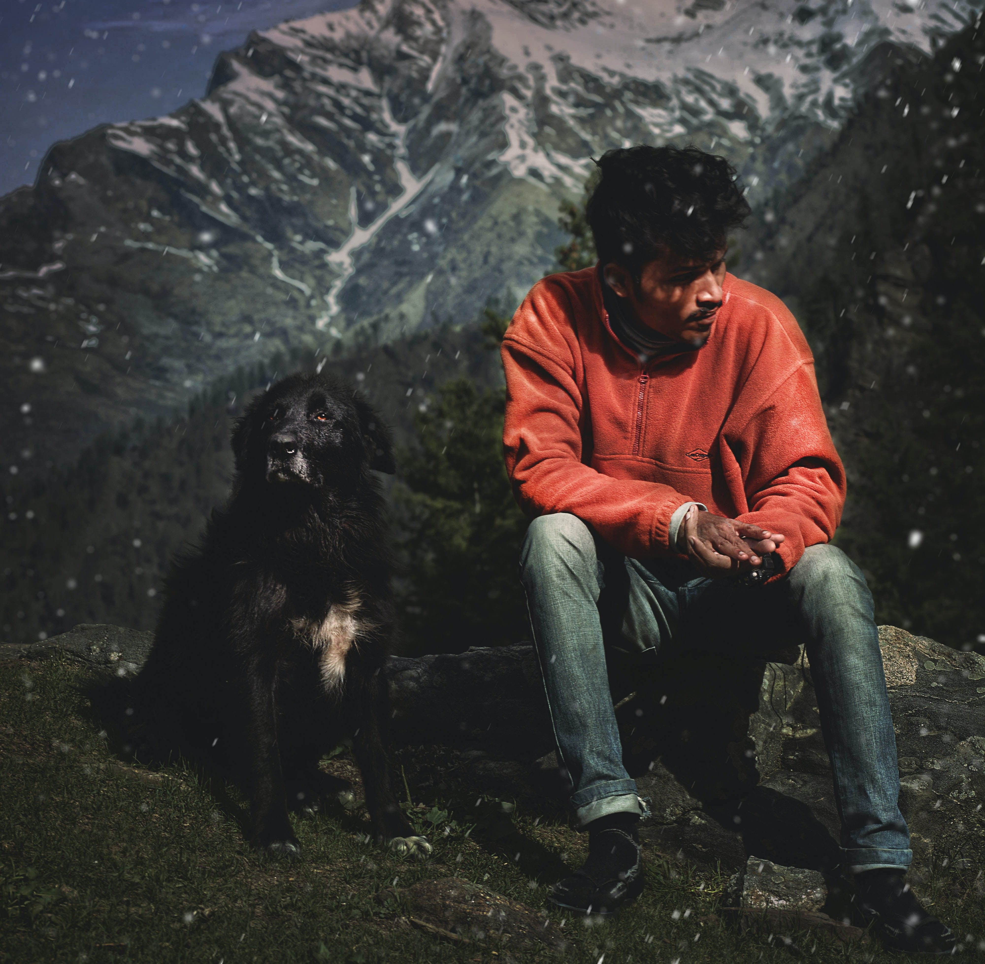 Man Sitting On Rock Next To A dog