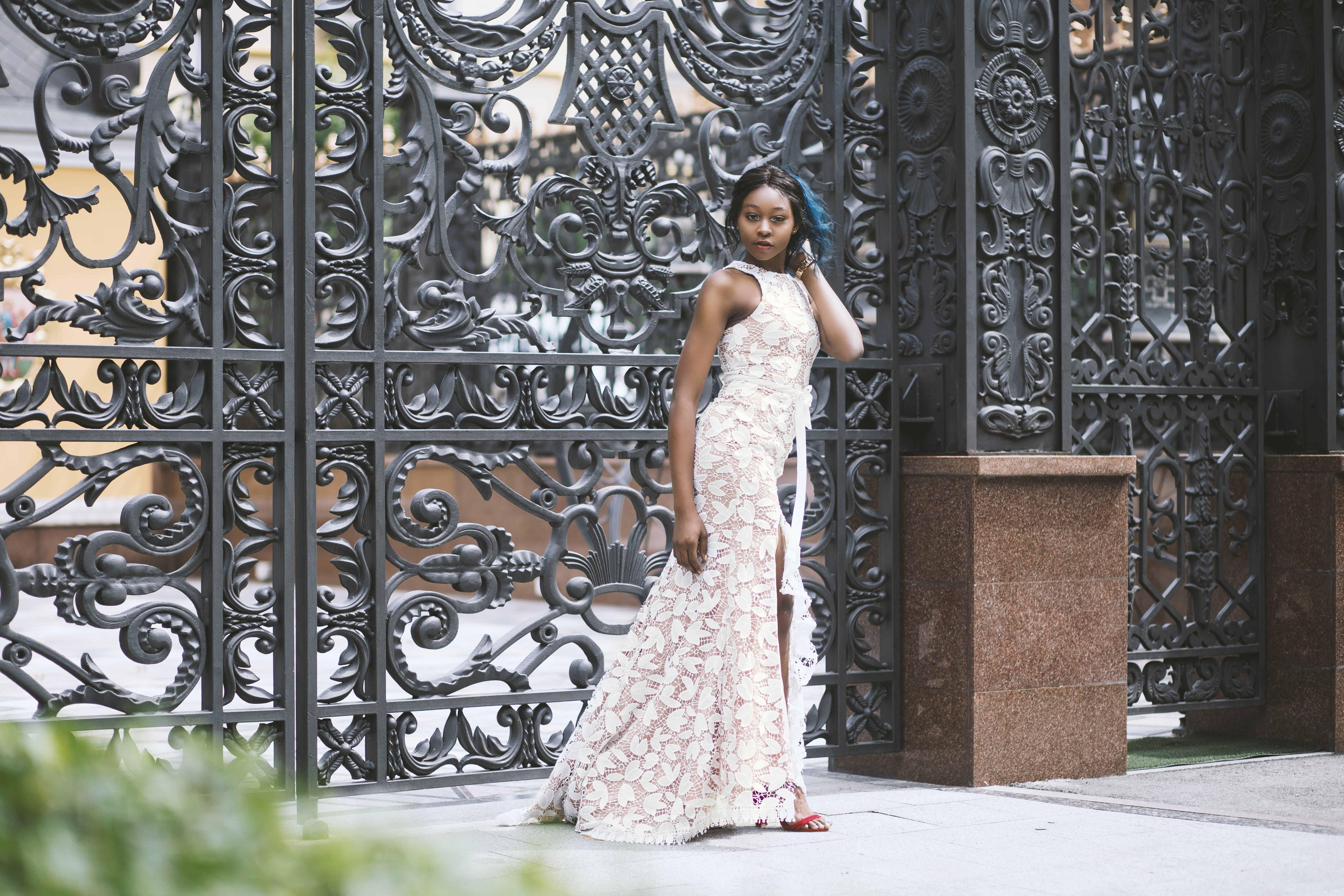 Woman Wearing White Dress Standing In Front Of Black Metal Gate