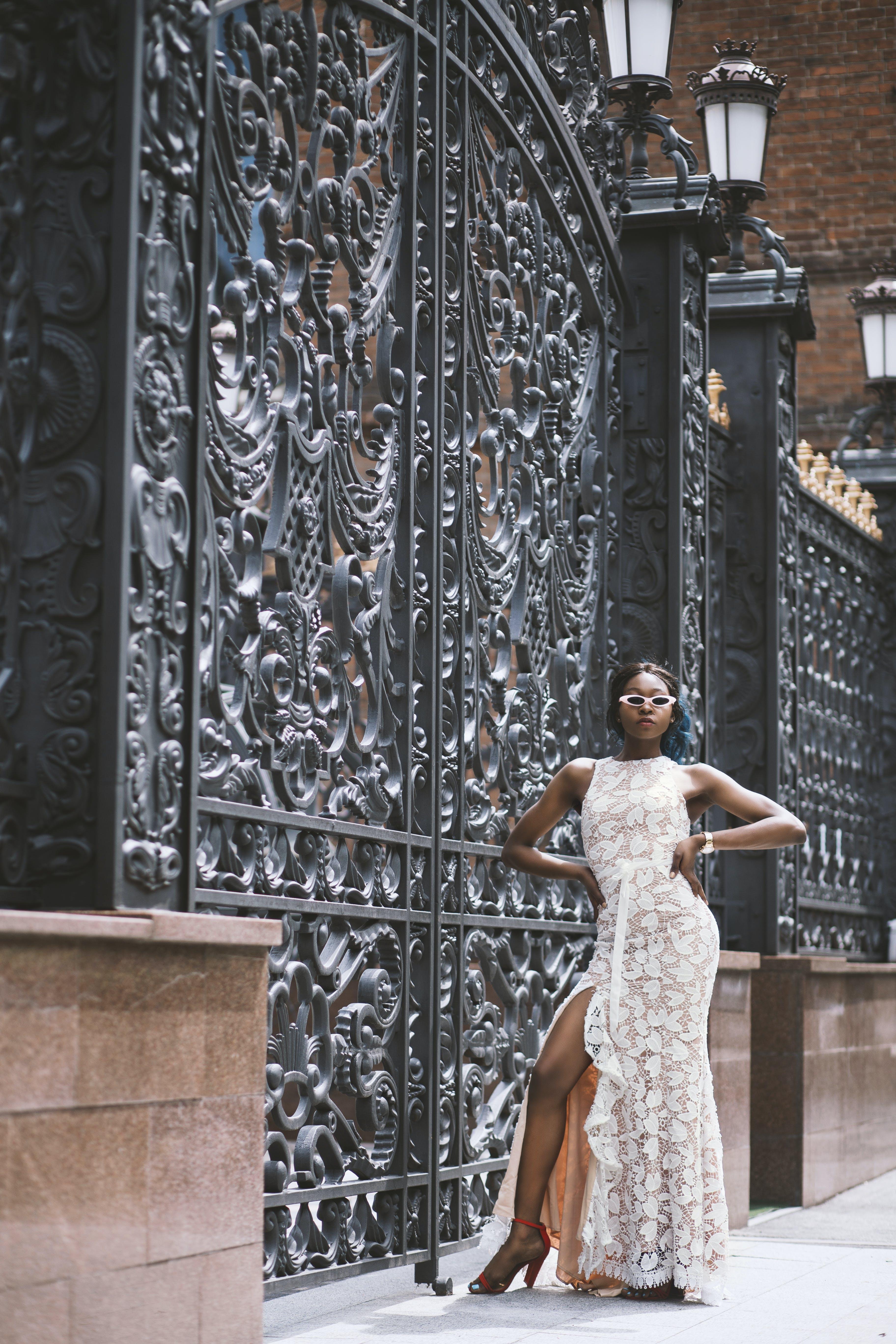 Woman Standing Beside Black Steel Gate