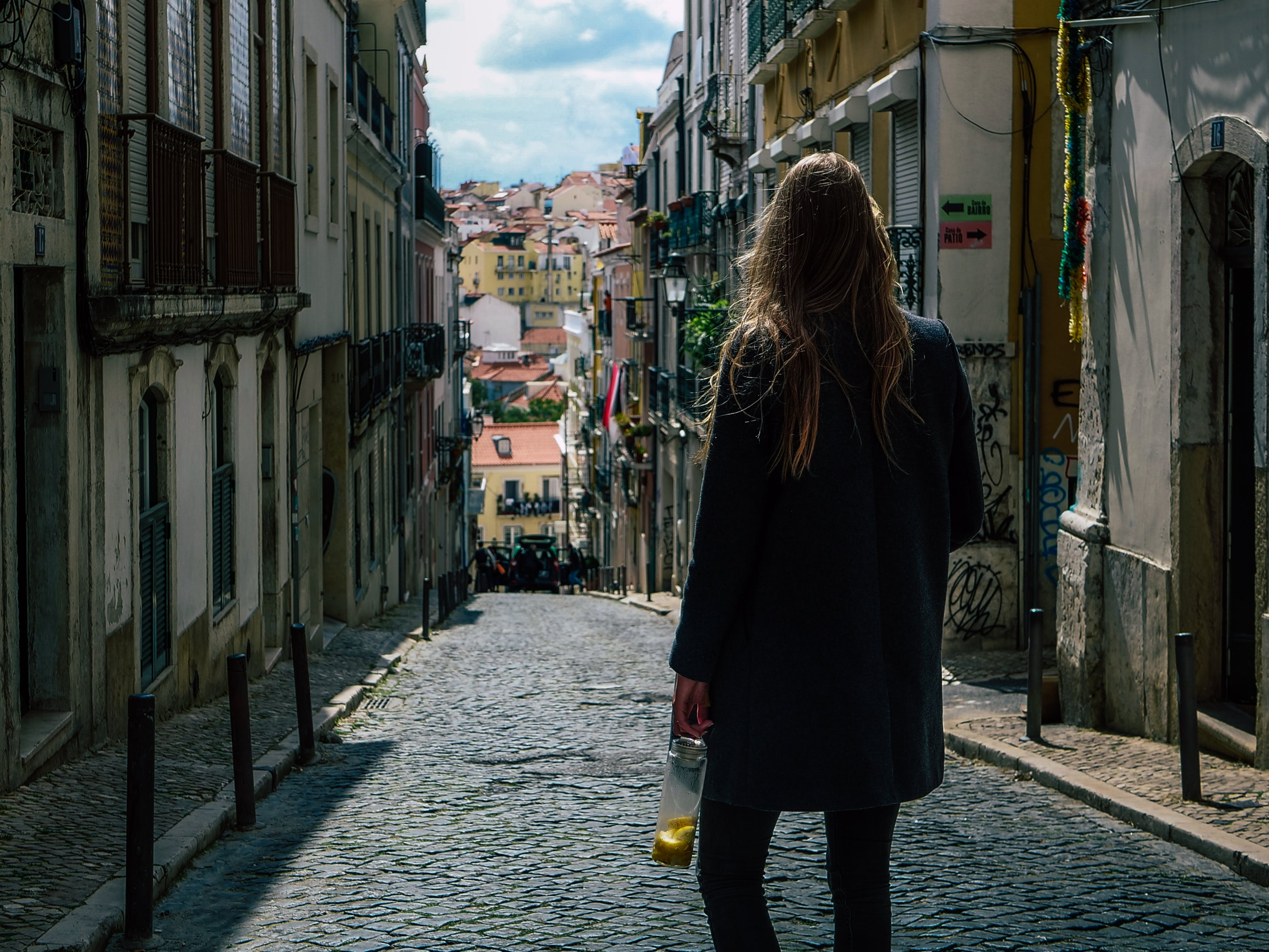 Woman in Black Coat Standing in Pathway Between Commercial Buildings