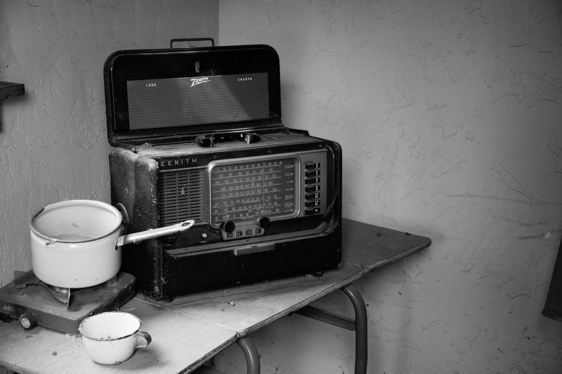 Grayscale Photo Of Vintage Radio Beside Stove With Cooking Pot