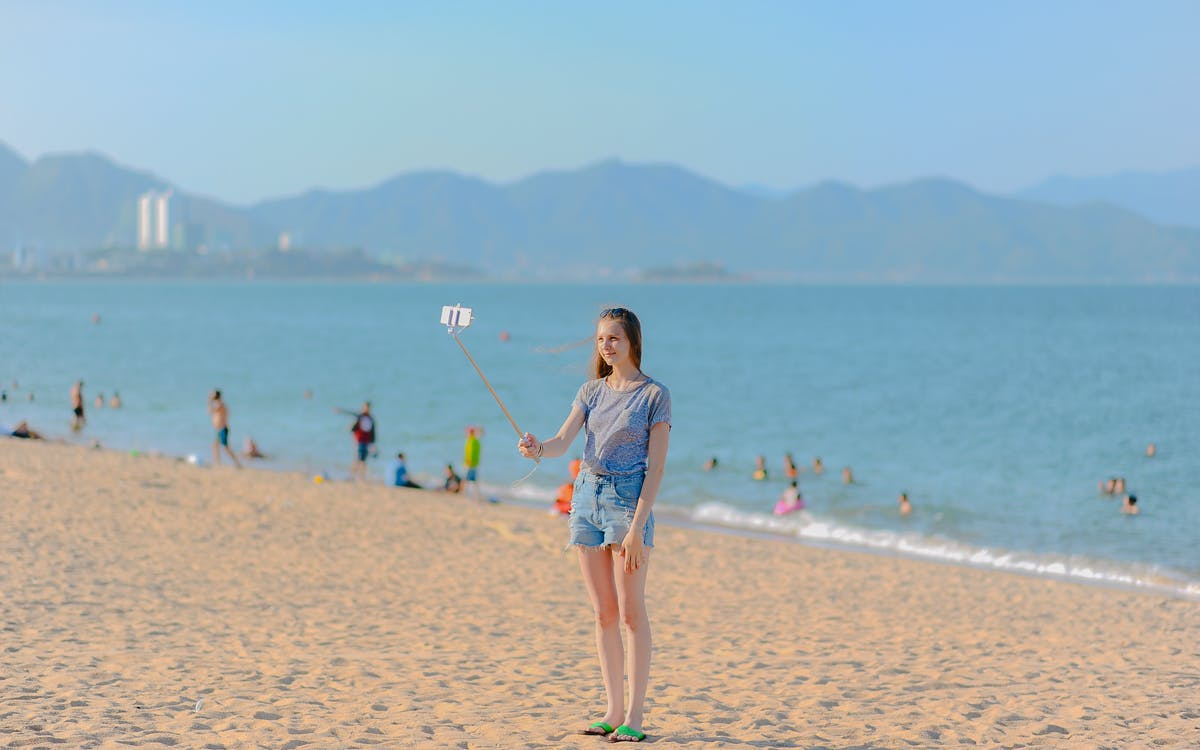 Woman Standing on Seashore Taking Selfie Using Monopod at Daytime