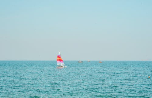 White and Pink Sailboat on Blue Ocean Water