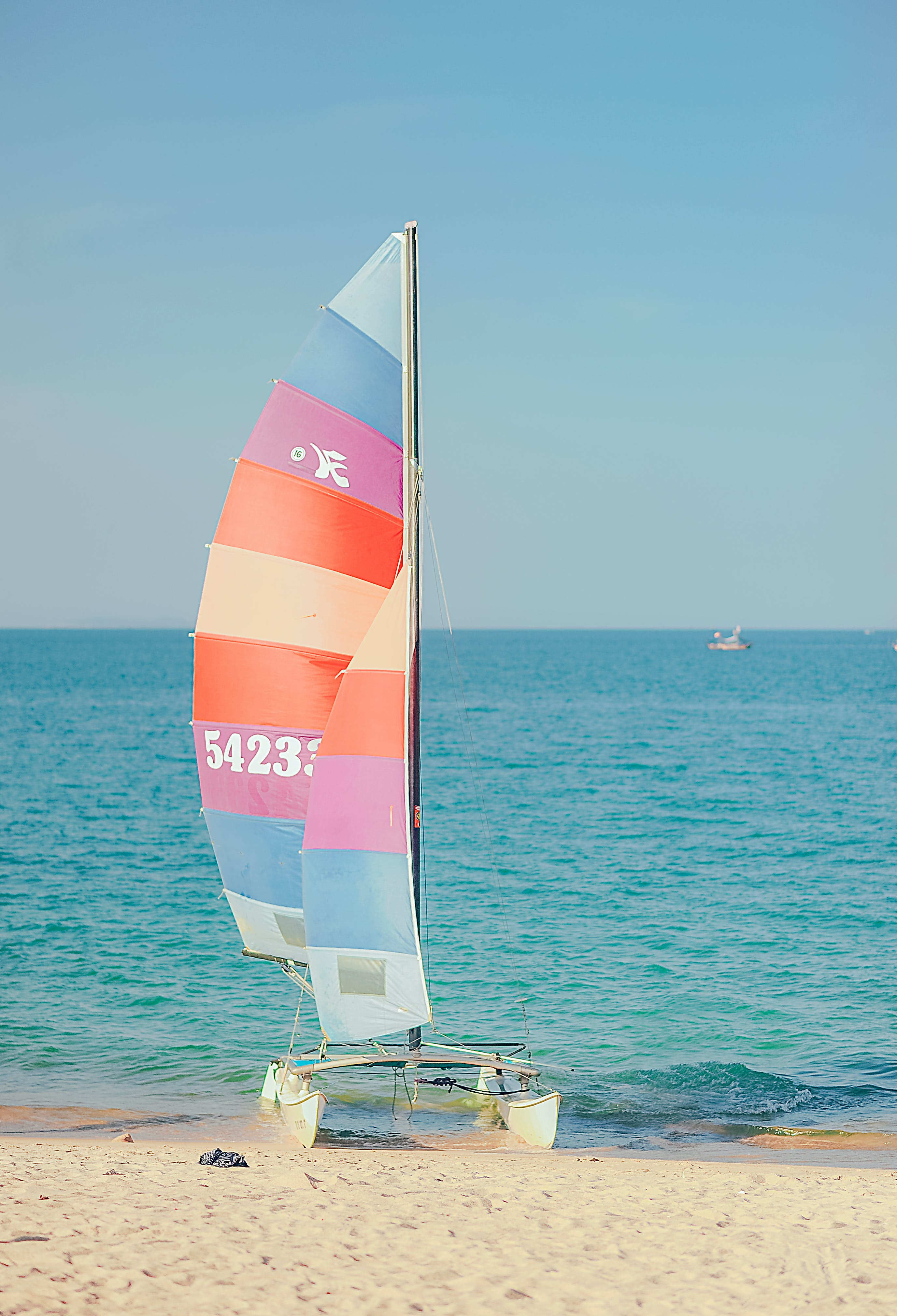 Multicolored Sail Boat on Shore Overlooking Sea Under Daytime Sky