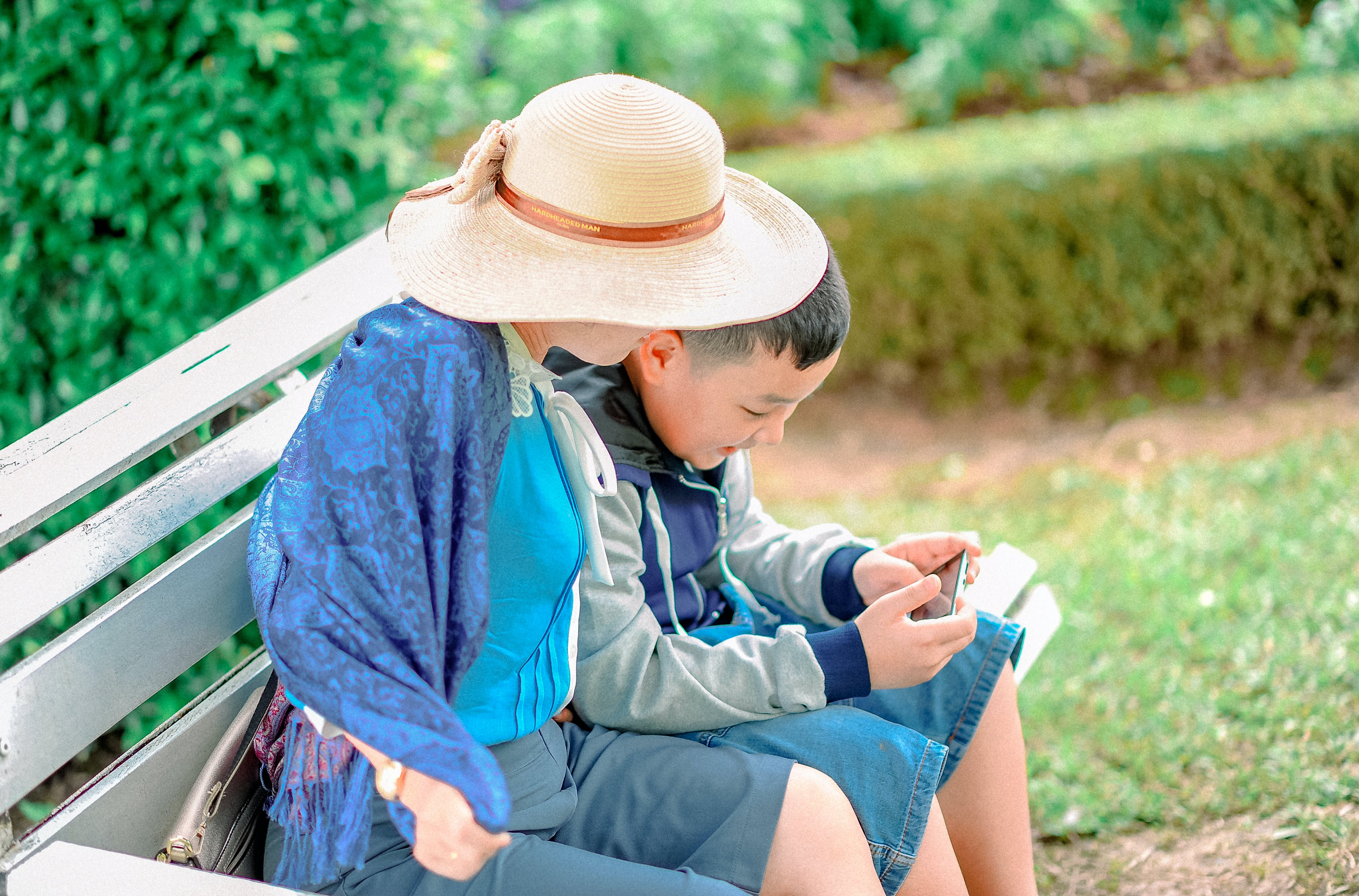 Boy Wears Gray, Blue, and Black Zip-up Jacket Holds Smartphone Next to Person Wears Beige Sun Hat Both Sits on Gray Wooden Bench