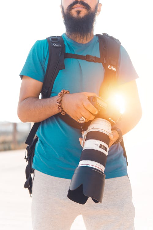 Man Holding Black And White Dslr Camera