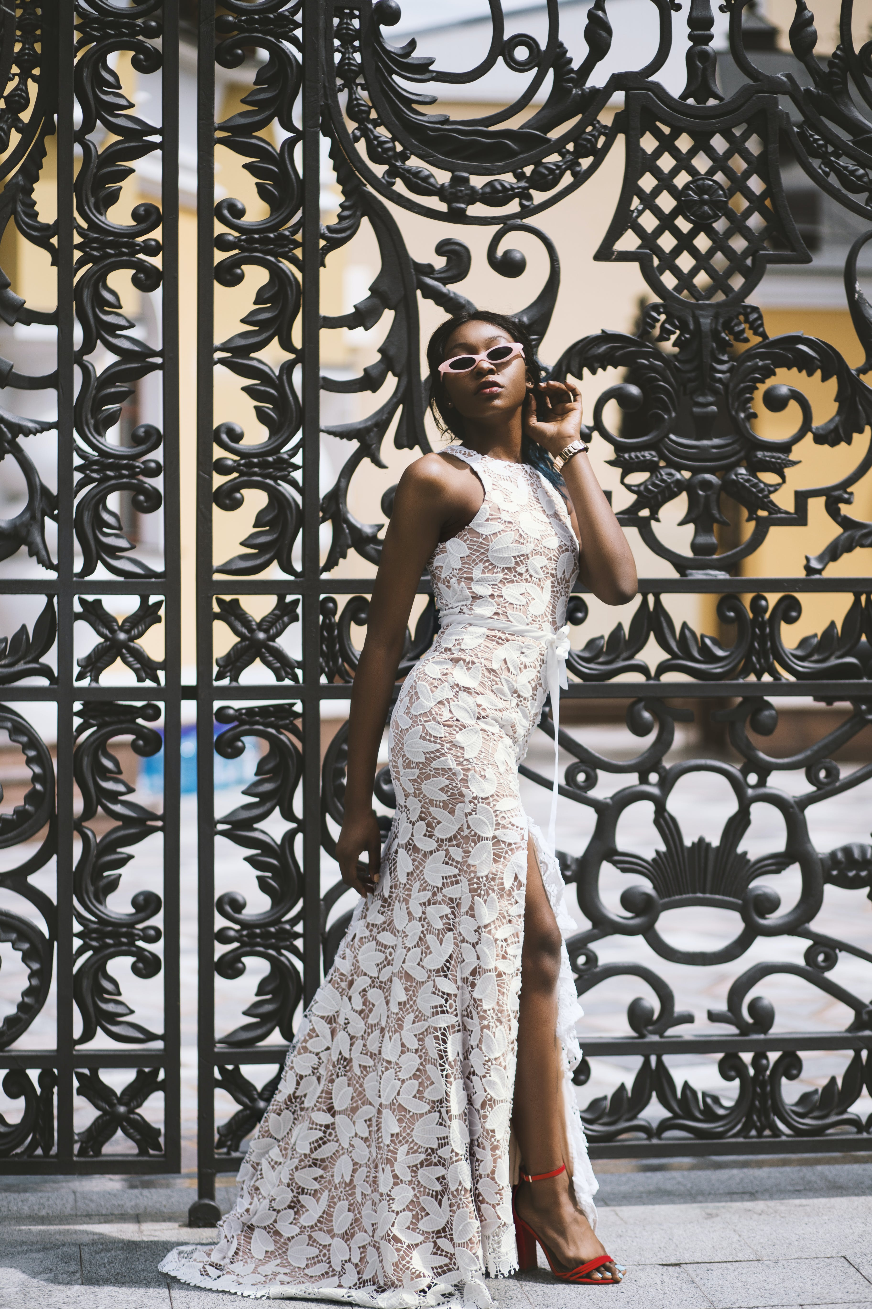 Woman Wearing White Floral Sleeveless Side-slit Maxi Dress Standing Beside Black Metal Gate