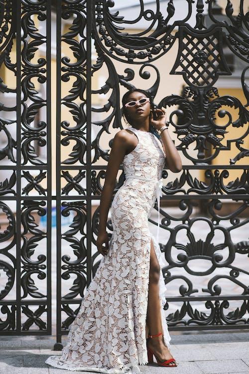 Woman Wearing White Floral Sleeveless Side-slit Maxi Dress Standing Beside Black Metal Gate
