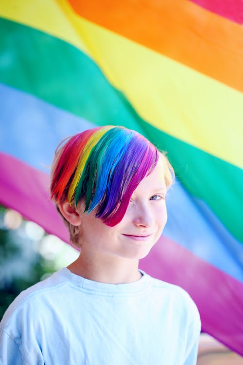 Boy Wearing White Shirt With Iridescent Hair Color Infront of Flag