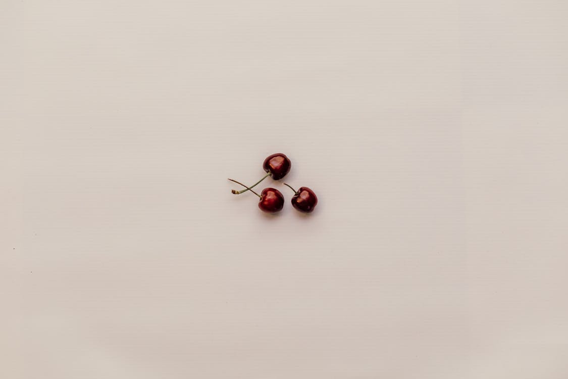 Three Red Cherry Fruits on White Surface
