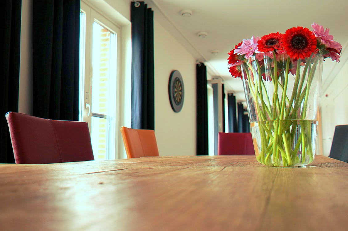 Red and Pink Anemone and Gerbera Daisy Flower Arrangement in Clear Glass Vase on Top of Brown Wooden Table
