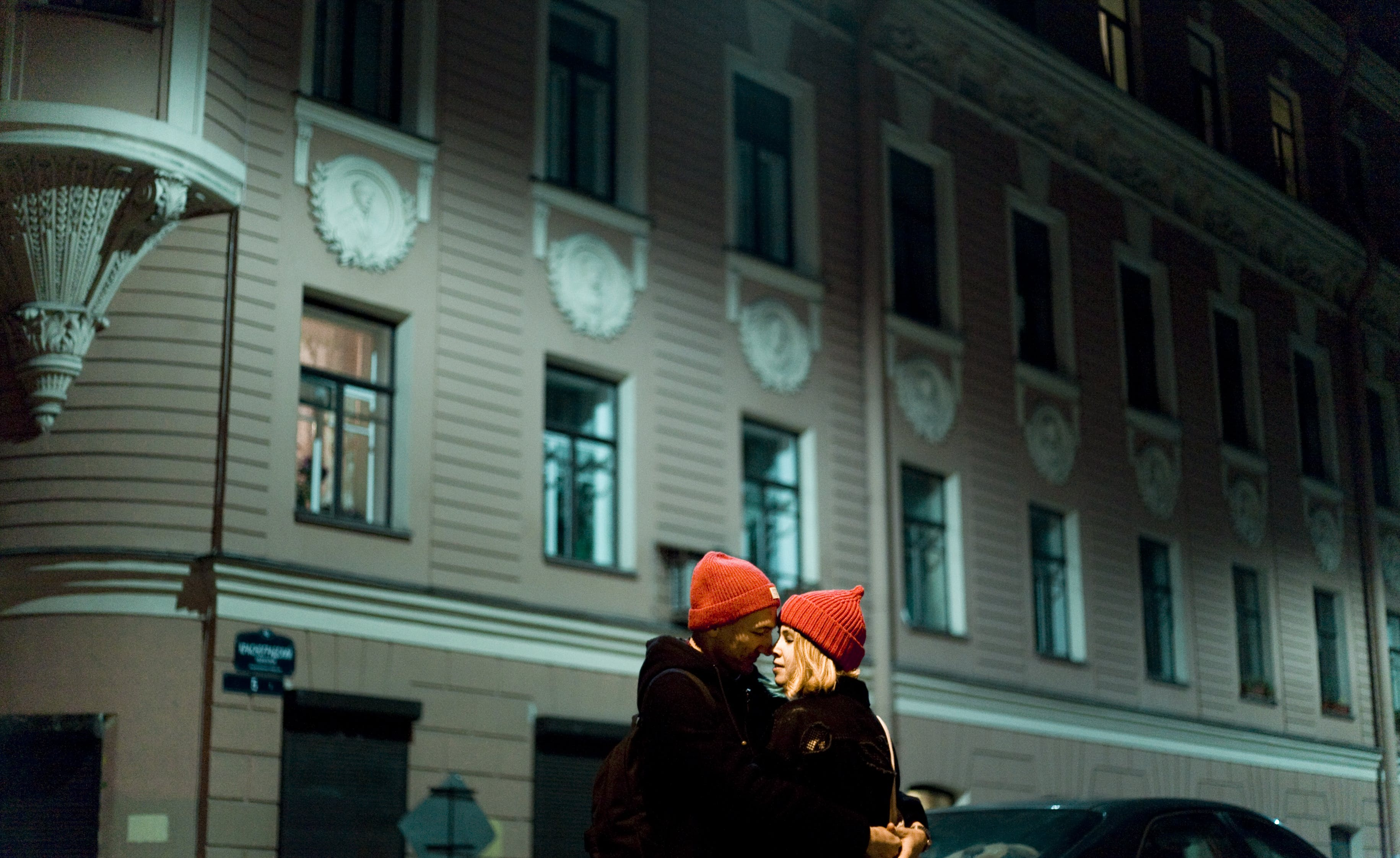 Man and Woman Wearing Red Knit Cap About to Kiss in Front of Gray Concrete Building during Nighttime