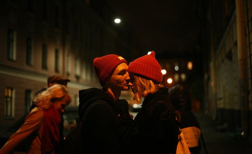 Man Kissing Woman's Nose Outdoor during Nighttime