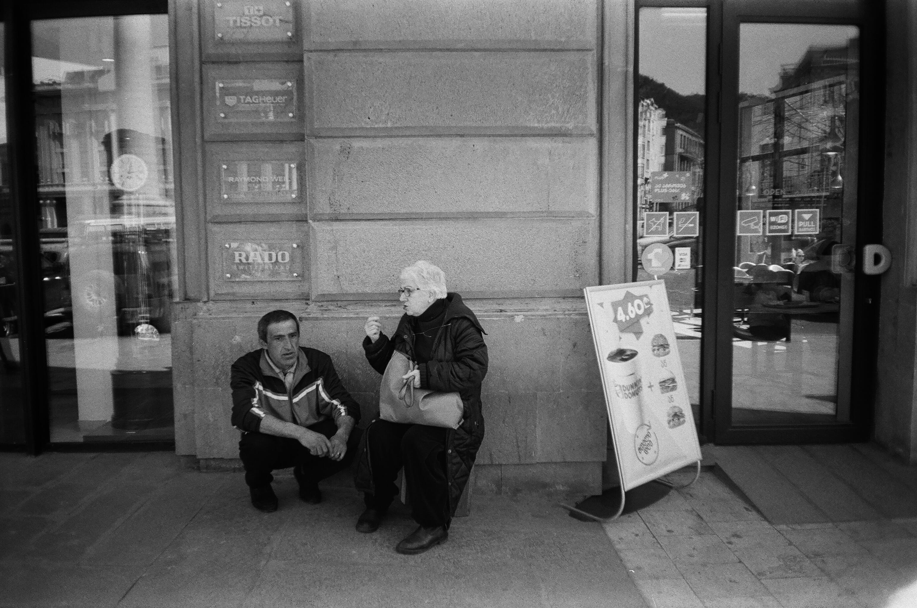 Two Men Sitting in Near Glass Door