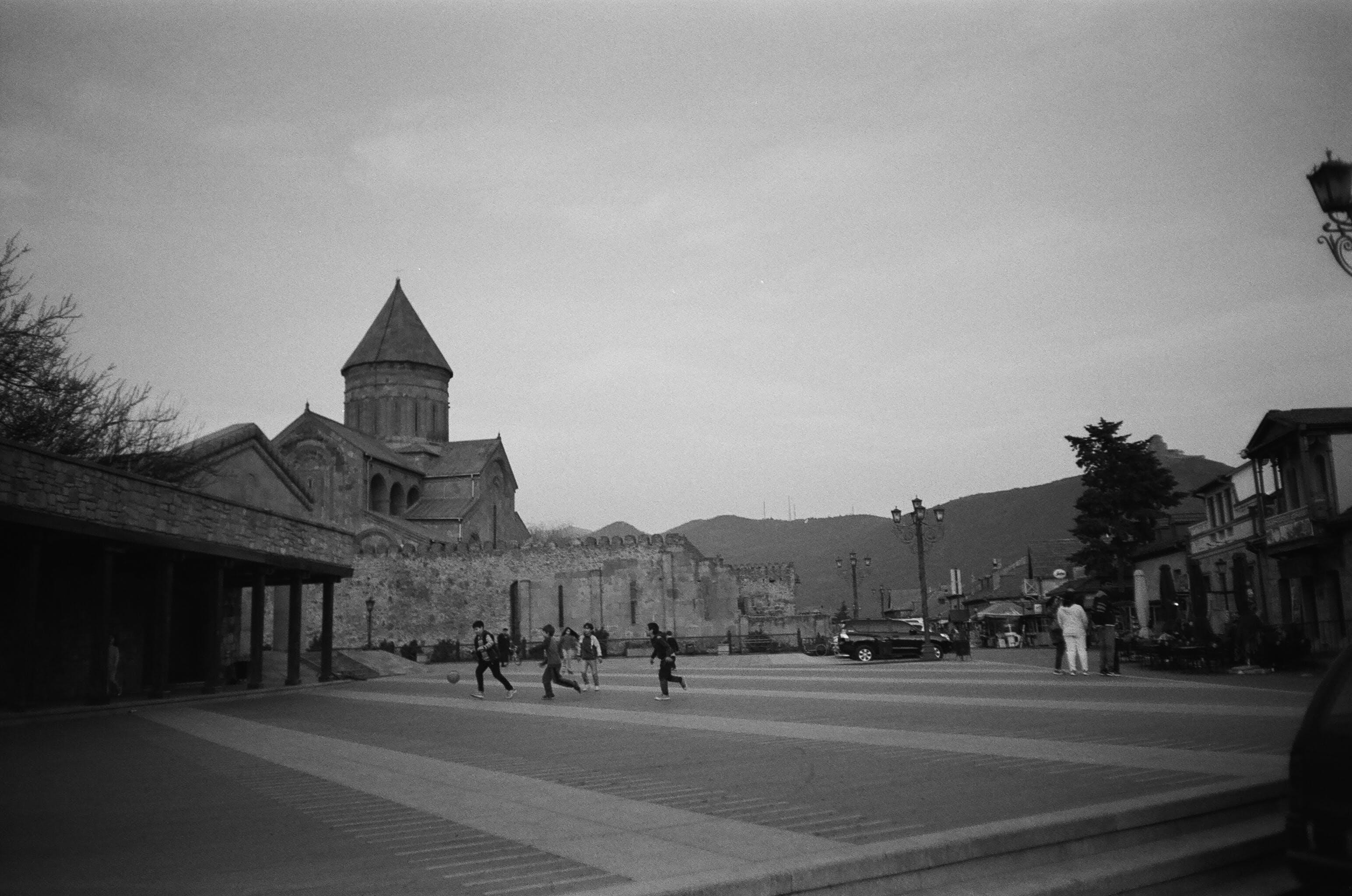 Grayscale Photo of People Between Buildings