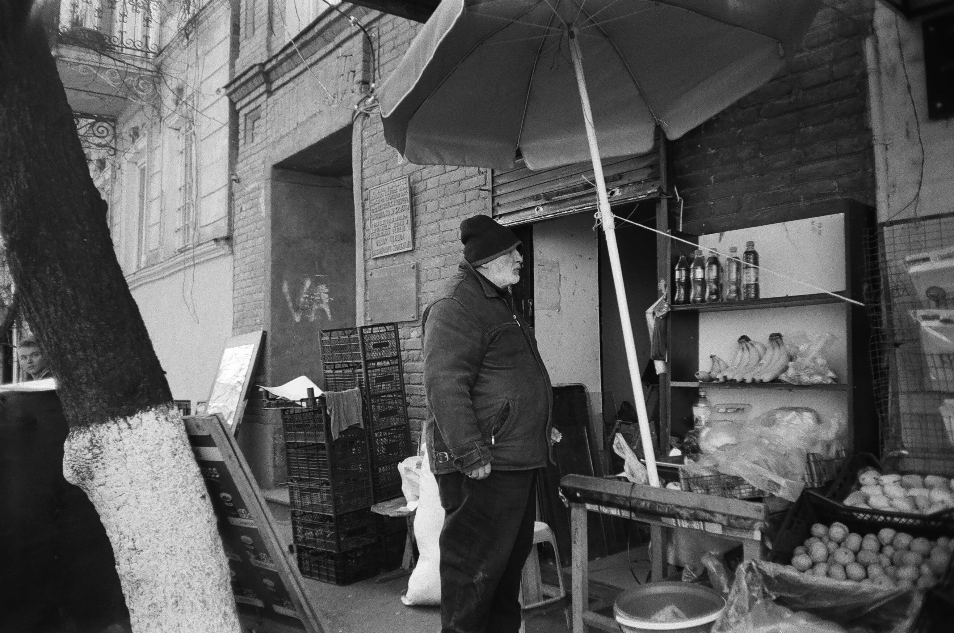 Gray Scale Photo of Man Standing Beside Street With Fruits
