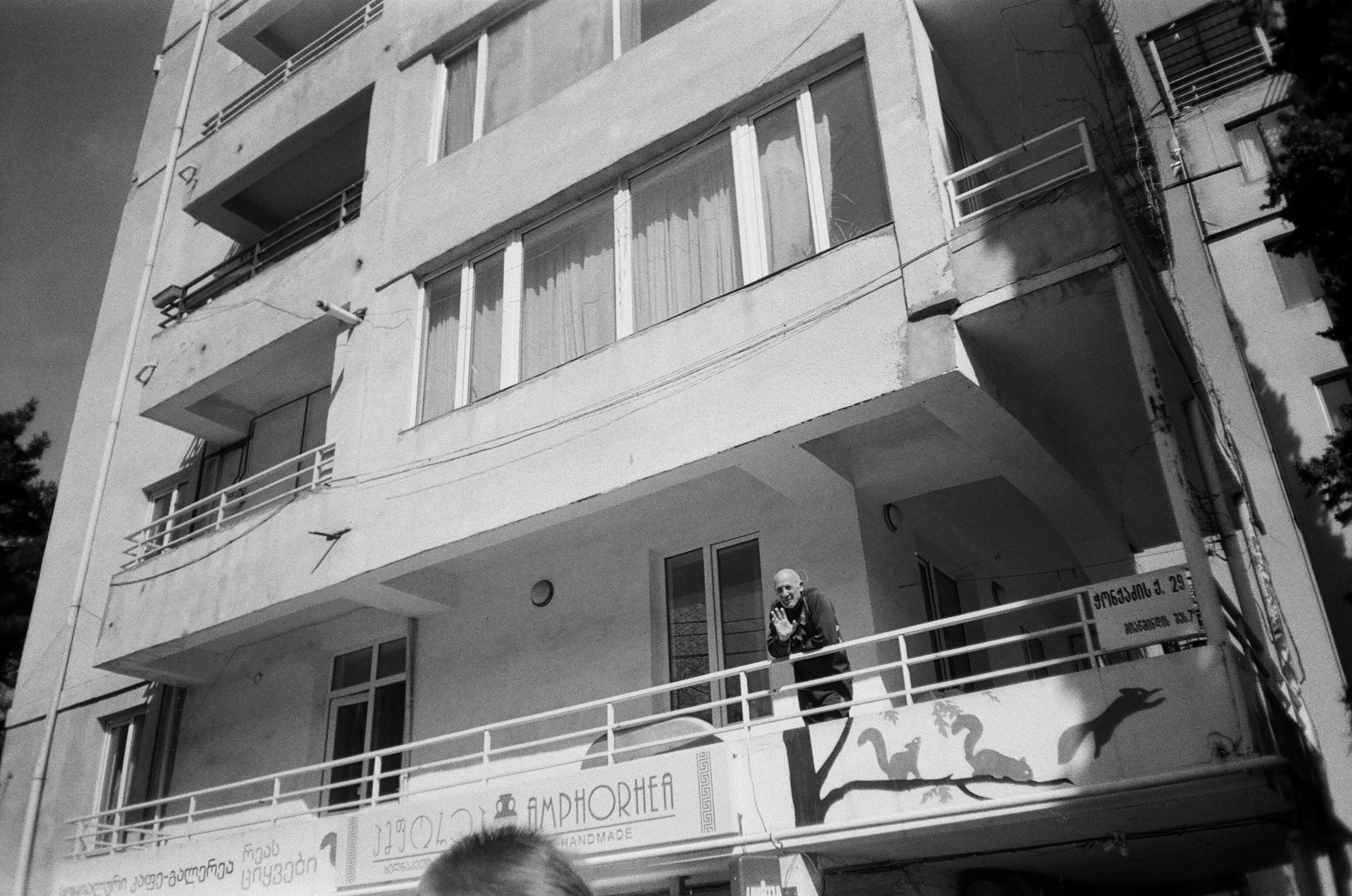 Greyscale Photo of Man Waving at Person While on Balcony of a Building