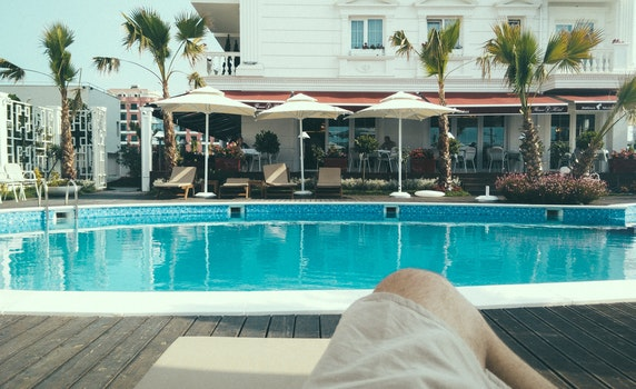 Person Relaxing Near a Swimming Pool