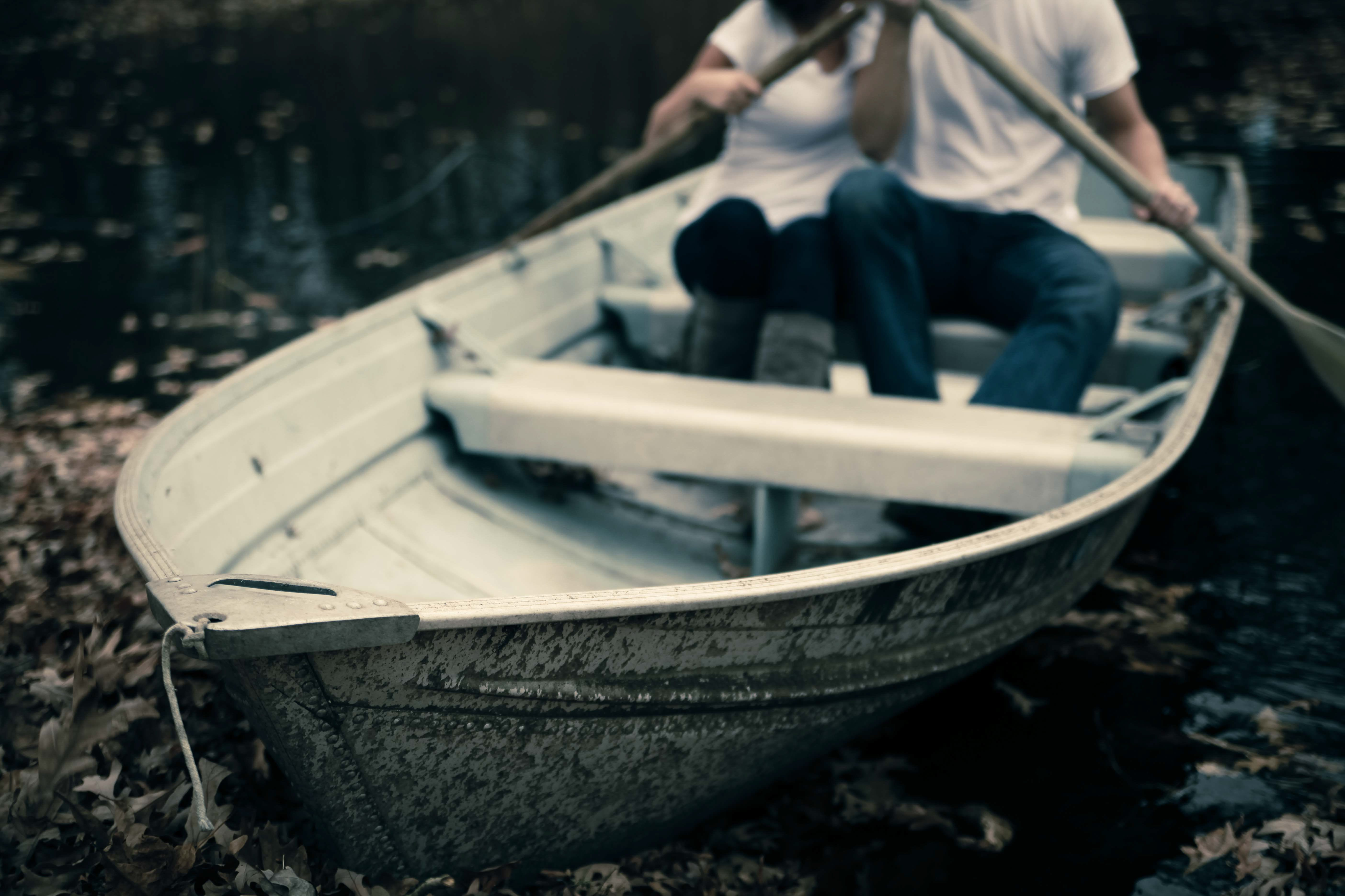 Man and Woman Sitting on Boat Holding Paddles