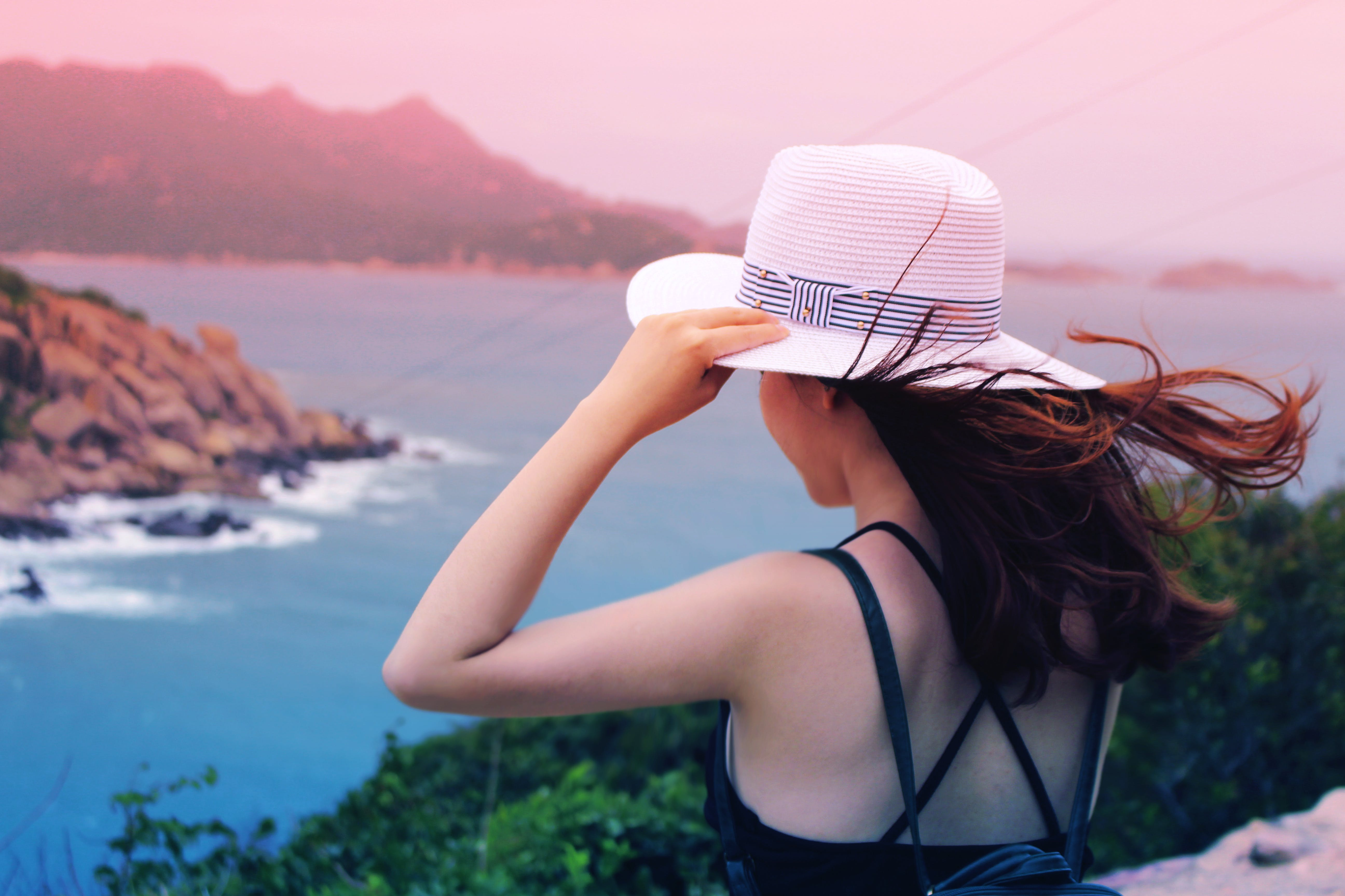 Wman Holding Wricker Shade Hat on Ocean View