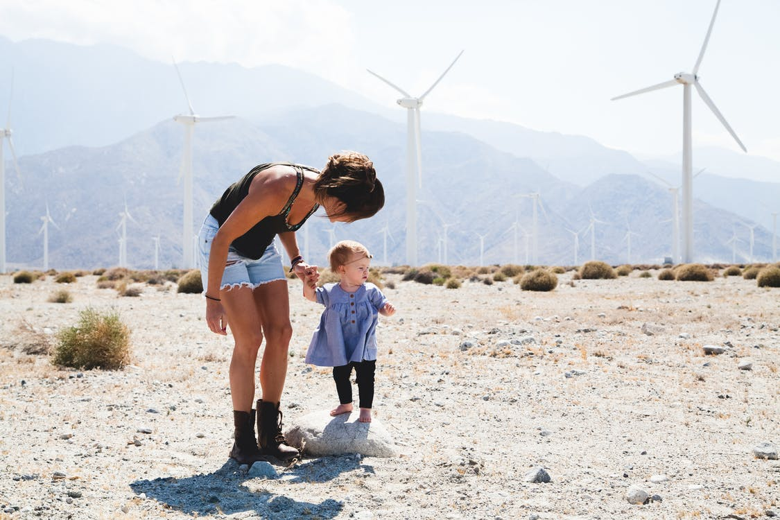 Woman Holding Her Child Walking Near Windmills