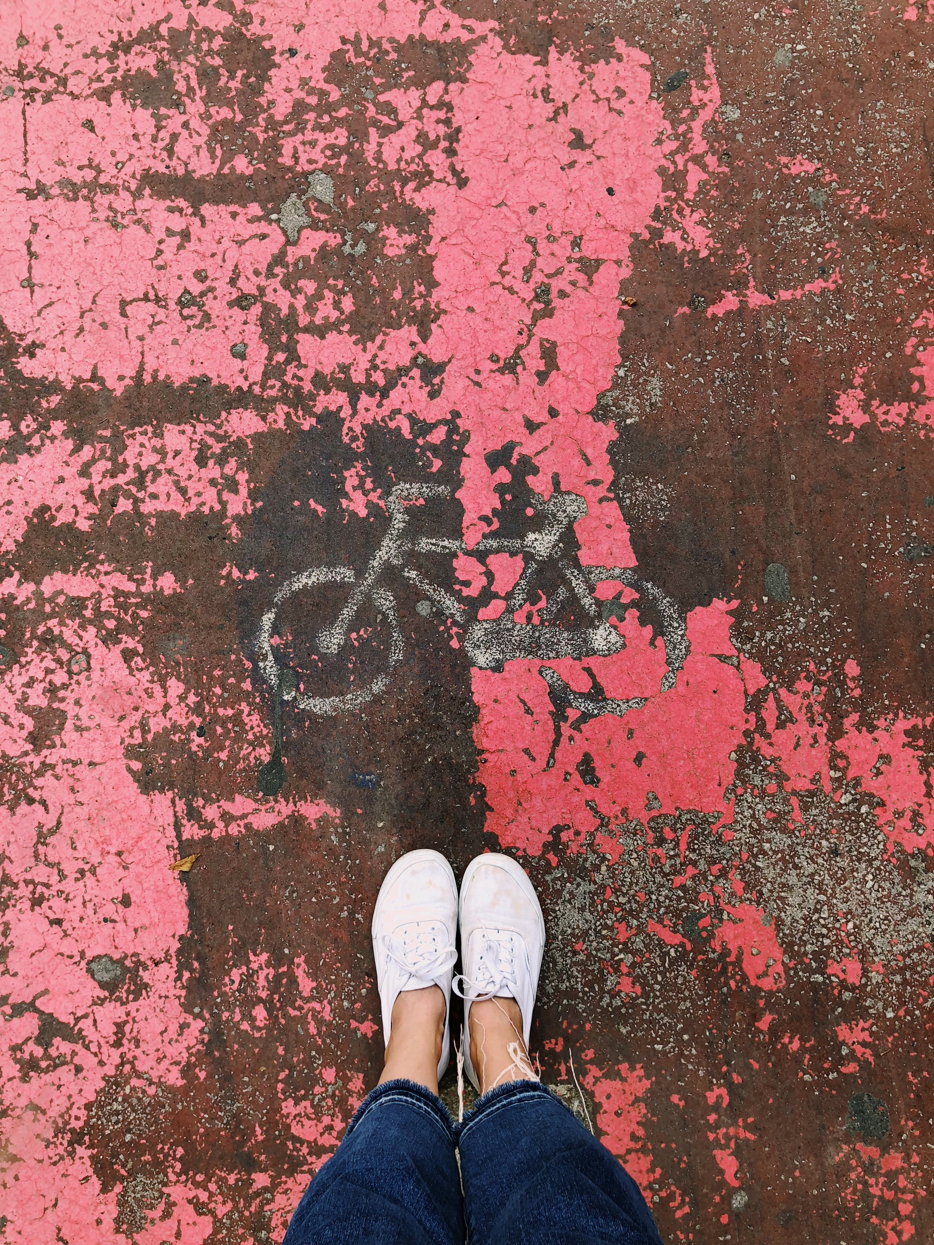 Person's Feet on Bicycle Artwork With Pink Background