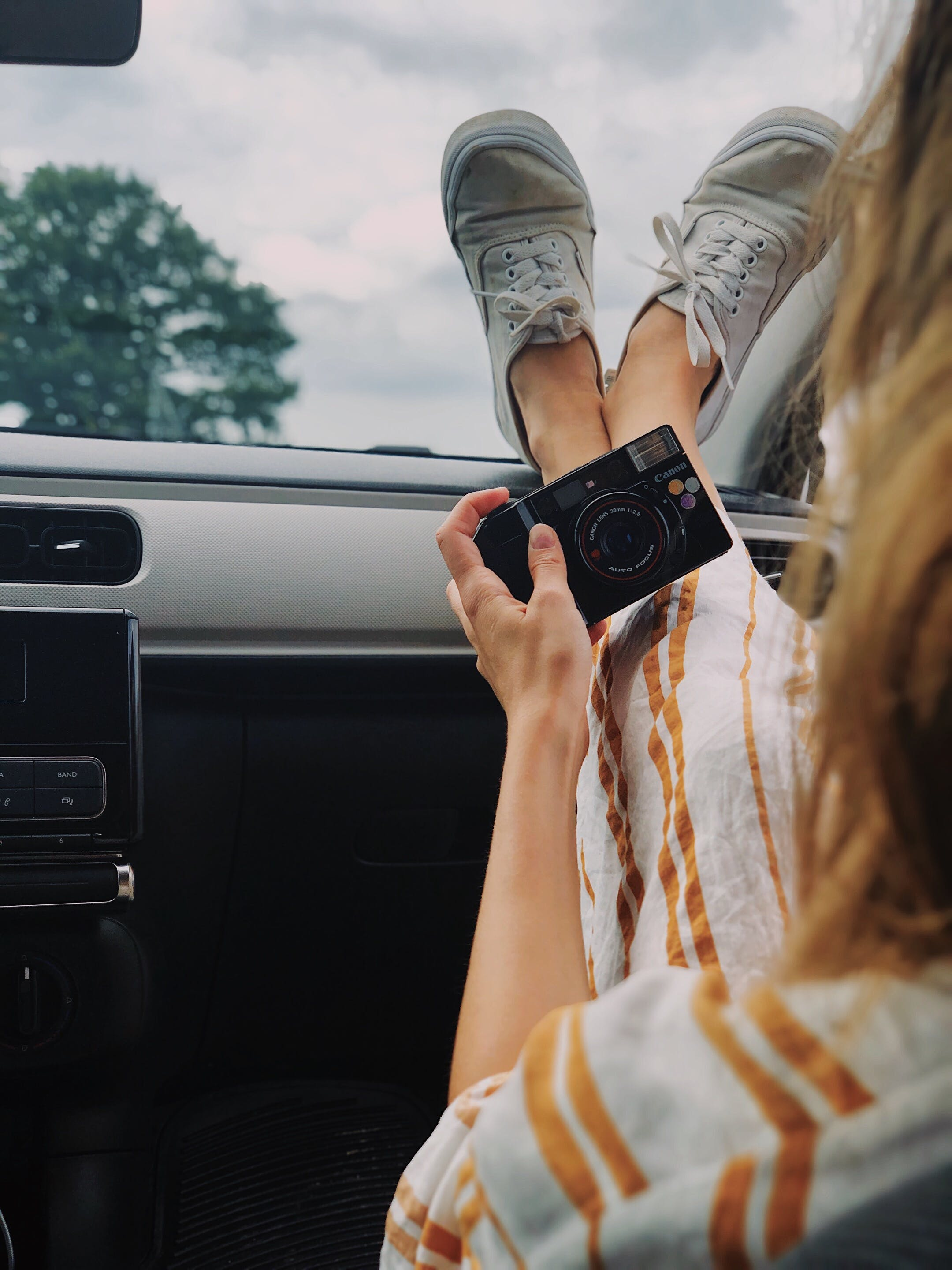 Woman Holding Compact Camera While Feet On Top Of Vehicle Dashboard