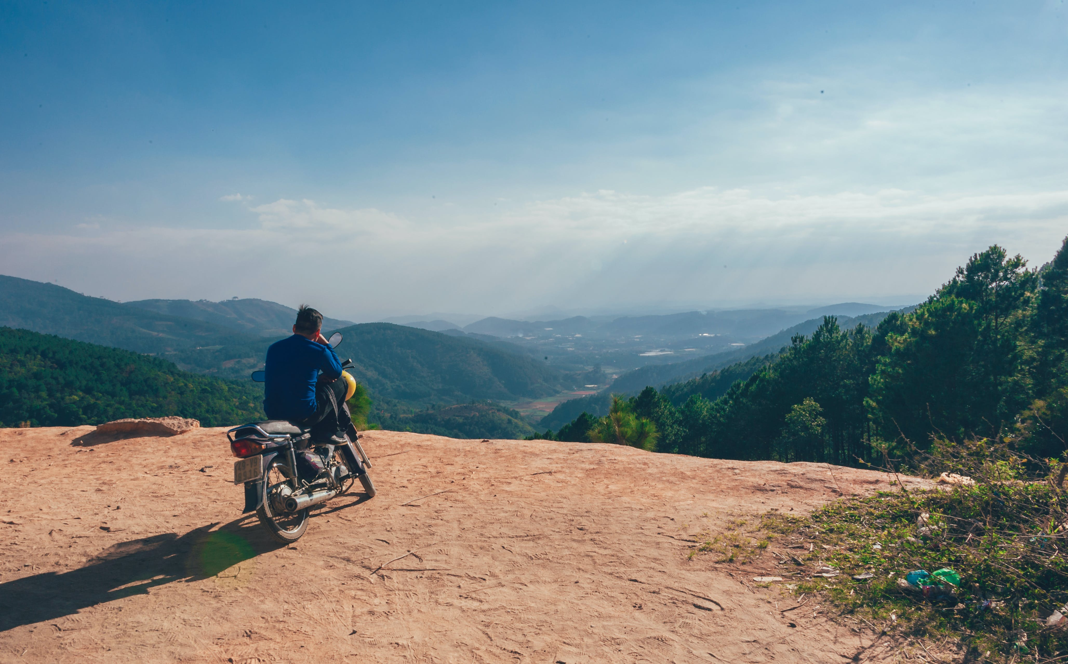 Man Sitting On Motorcycle Facing Mountains