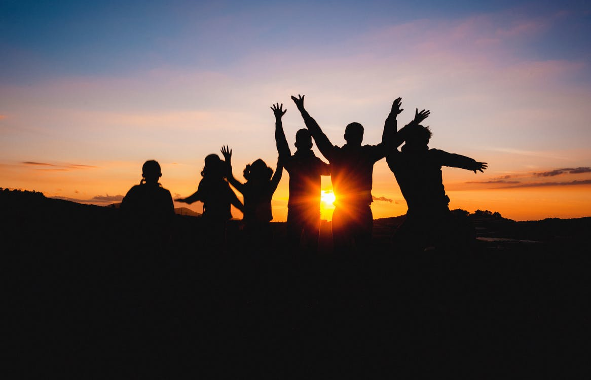 Silhouette Of People Raising Hands During Golden Hour