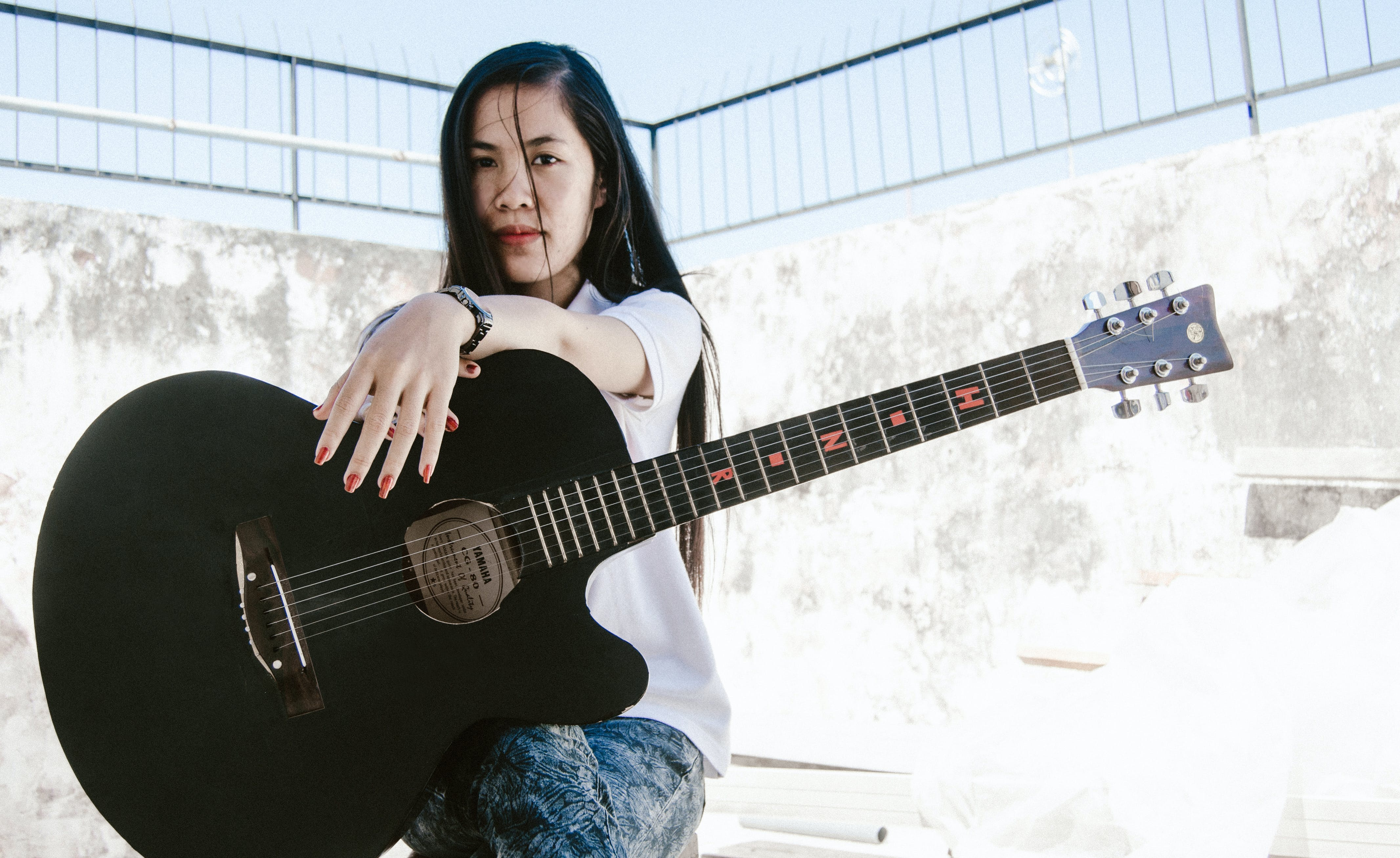 Woman Holding Black Acoustic Guitar