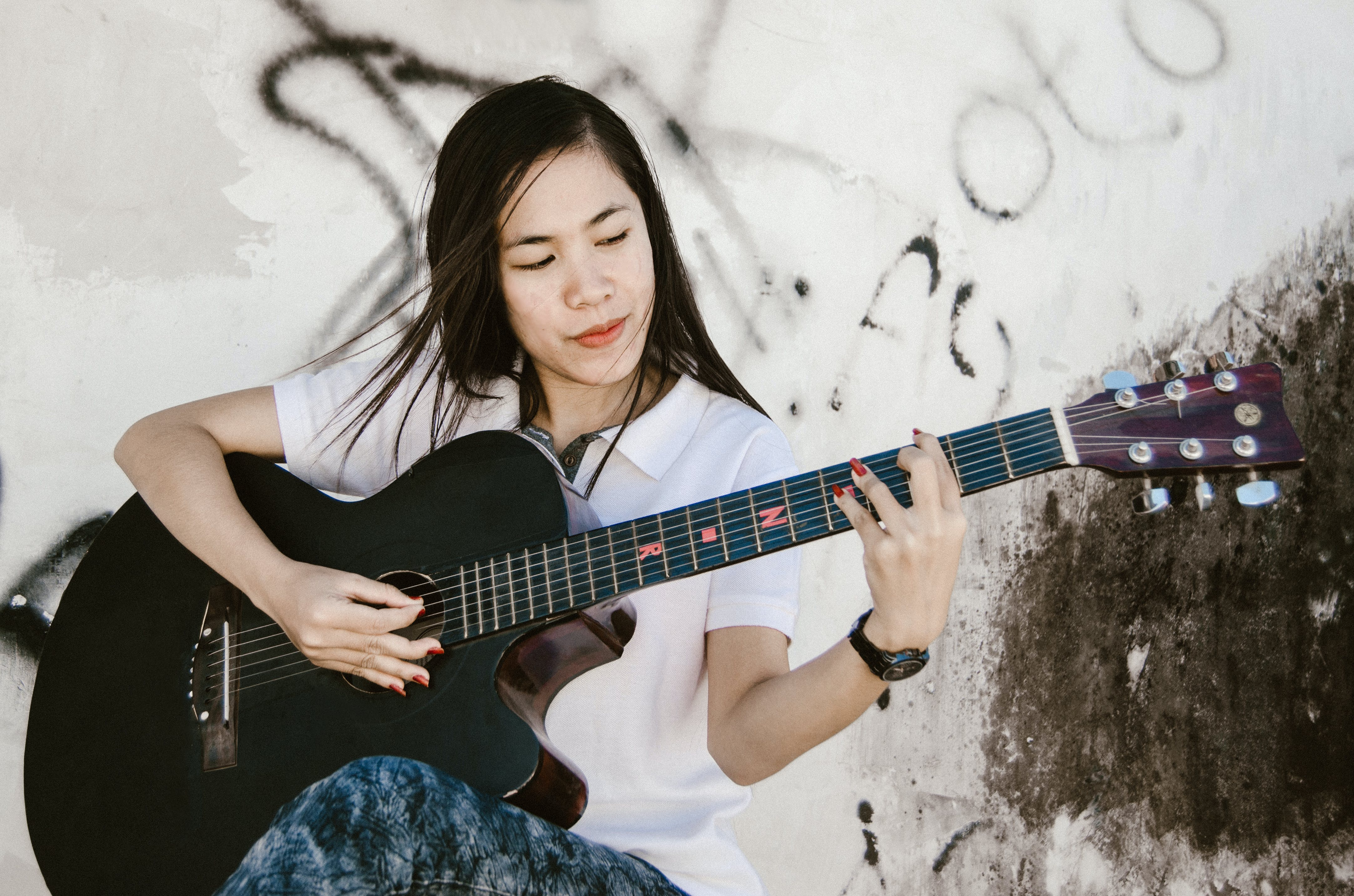 Woman Playing Black Acoustic Guitar