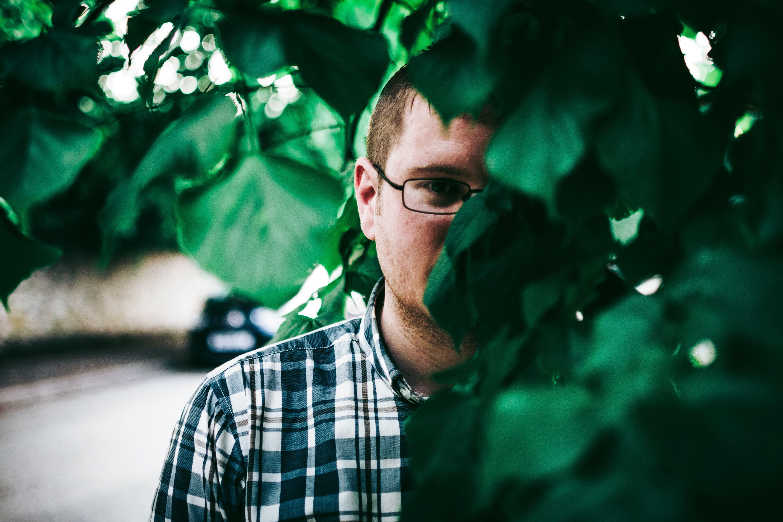 Man In Eyeglasses Standing Behind Green Leaves