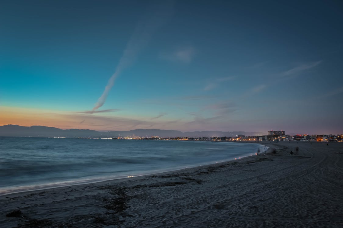 People on Beach's Seashore during Sunset