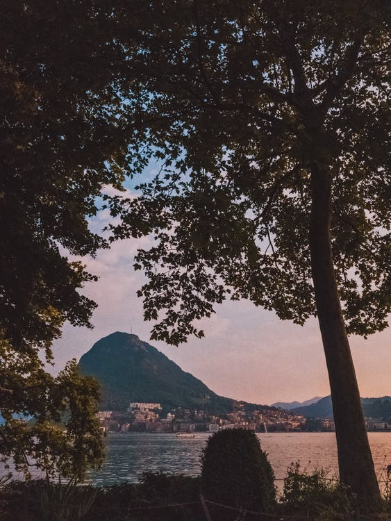 Silhouette Photography of City Near Body of Water and Mountain