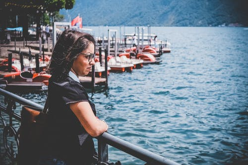 Woman Standing Beside Railings at a Dock