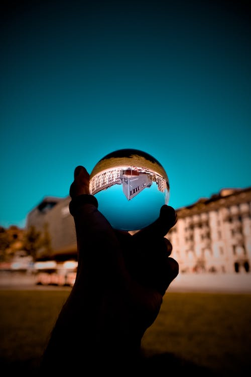 Shallow Photography of Person Holding Clear Glass Ball